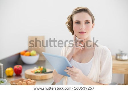 Young thoughtful woman standing in kitchen holing her tablet at home - stock photo