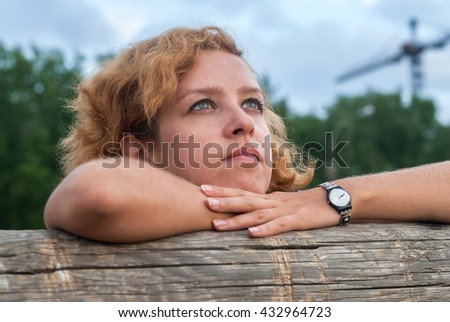 Young thoughtful woman with freckles at construction background - stock photo