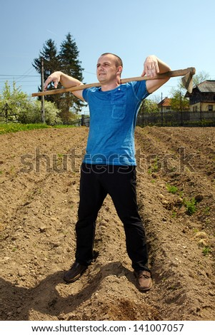 Young tiller working the land with a hoe in a sunny day - stock photo