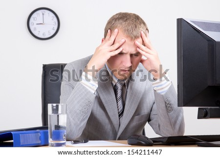 young tired businessman sitting in his office - stock photo