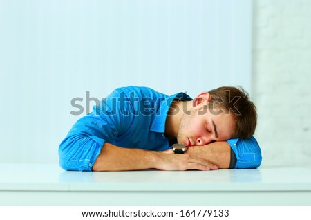 Young tired businessman sleeping at workplace in office - stock photo