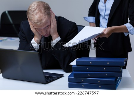 Young tired employee and his demanding female boss at work - stock photo