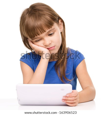 Young tired girl is using tablet while sitting at table supporting her head with hand, isolated over white - stock photo