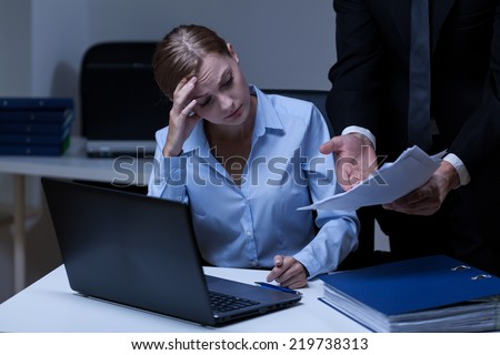 Young tired secretary at work with her boss - stock photo