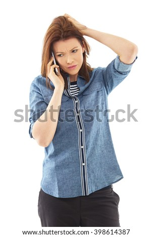 Young tired, stressed woman in blue shirt talk over her mobile phone - stock photo