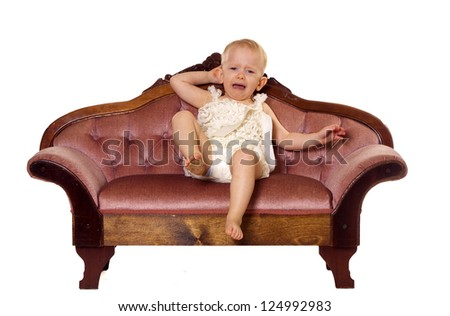 Young todderl having a temper fit. Sitting on a time-out couch. - stock photo