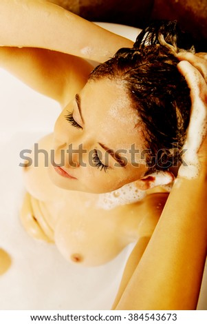Young topless woman washing hair in bath - stock photo