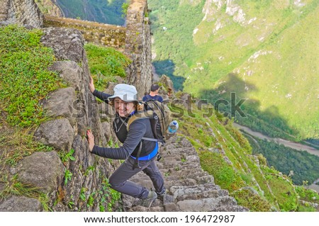 Young tourist climbing Huayna Picchu (Machu Picchu, Peru) - stock photo