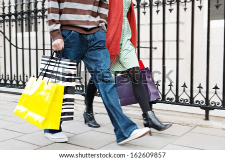Young tourist couple on vacation walking down an exclusive shopping street in the city of London with classic stone buildings and holding carrier paper bags, outdoors. - stock photo