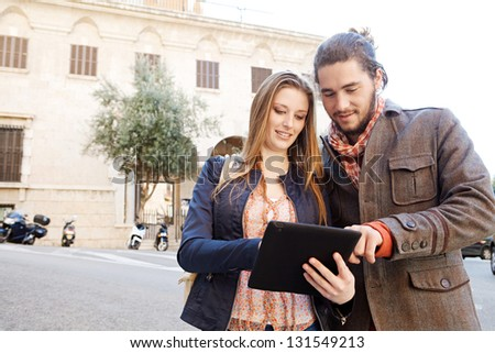 Young tourist couple standing together in a destination city holding and sharing a digital tablet pad while on vacation, smiling. - stock photo