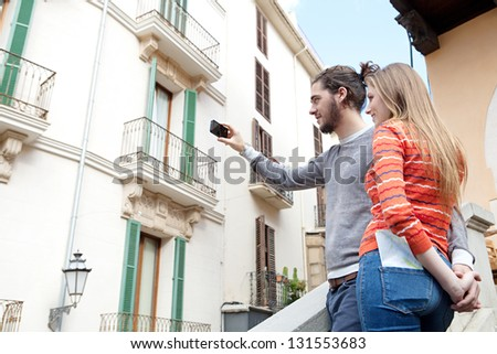 Young tourist couple standing together in a destination city taking pictures of the classic buildings and holding hands during a sunny day. - stock photo