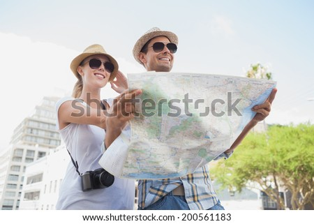 Young tourist couple using the map on a sunny day in the city - stock photo