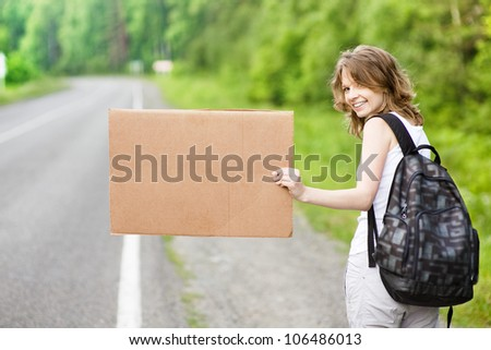 young  tourist hitchhiking along a road with message board - stock photo