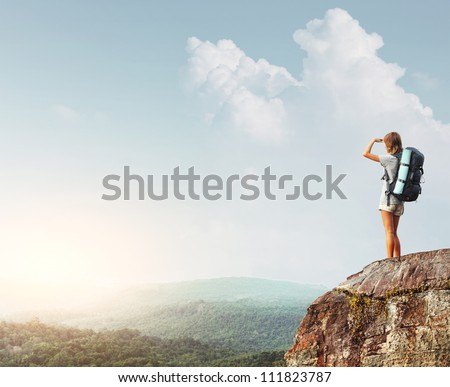 Young tourist with backpack standing on top of a mountain and enjoying morning valley view - stock photo