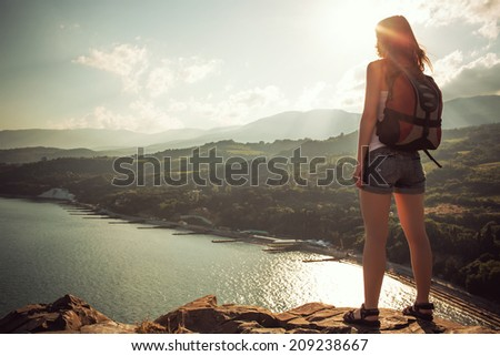 Young tourist woman on the top of the mounting with pleasure looking at a beautiful sea landscape and sun - stock photo