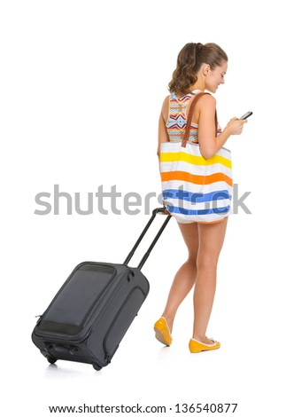 Young tourist woman with wheel bag writing sms . rear view - stock photo