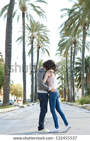 Young touristic couple hugging in a palm trees boulevard while visiting a destination city on holiday. - stock photo