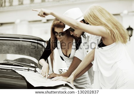 Young tourists with a road map against retro car - stock photo