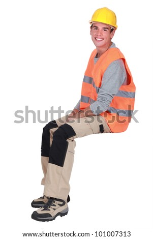 Young tradesman sitting on an invisible block - stock photo