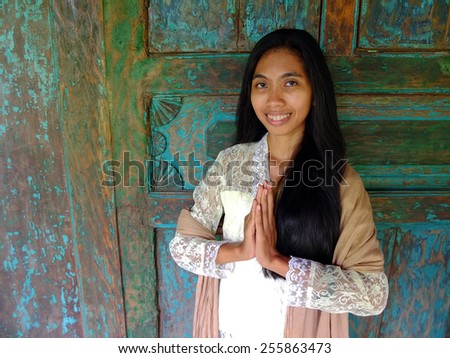 Young traditional Asian woman greeting in front of wooden house. - stock photo