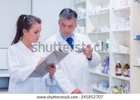 Young trainee writing on a prescription pad in the pharmacy - stock photo
