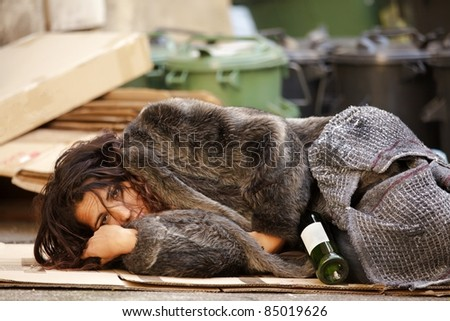 young tramp woman lying among trash with bottle of wine - stock photo