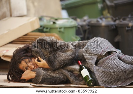 young tramp woman lying with bottle of wine  in bin - stock photo