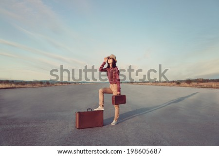 Young traveler hipster woman with retro suitcase looks through binoculars on road - stock photo