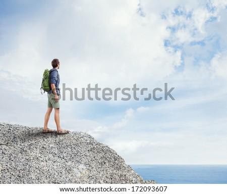 Young traveler looking at ocean - stock photo