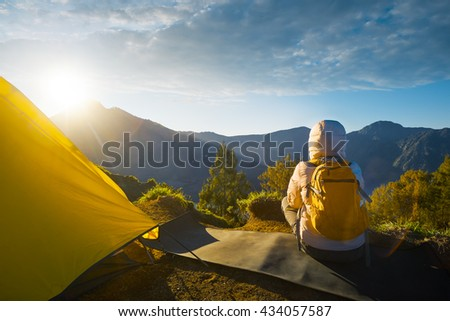 Young traveler with backpacker enjoying sunrise view at summit top in high mountain volcano Rinjani. Island Lombok, Indonesia. Traveling along mountains, freedom and active lifestyle concept - stock photo