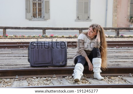 Young traveling woman sitting with suitcase along the train tracks, smiling - stock photo
