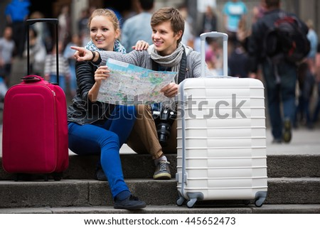 Young travellers couple with city map and baggage looking for hotel - stock photo