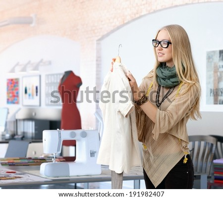Young trendy blonde caucasian fashion designer woman working at studio. Happy, table with sewing machine. - stock photo