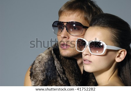 young trendy couple on gray - stock photo