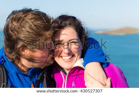 Young trendy kissing and hugging couple in Ireland wearing outdoor gear with the Irish sea in the background - stock photo