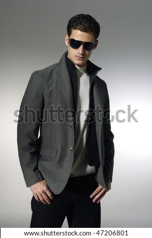 young trendy male model wearing sunglasses - stock photo