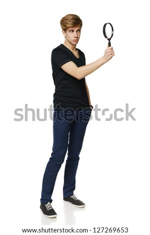 Young trendy man in full length looking trough the magnifying glass, over white background - stock photo