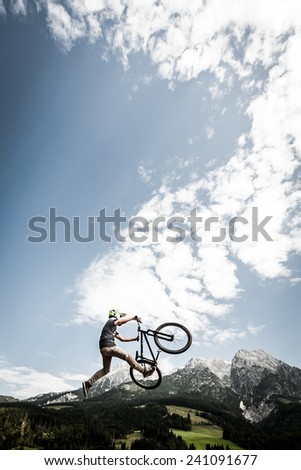 young trick stunt biker jumps trick high over alp mountains - stock photo
