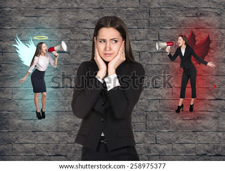 Young troubled businesswoman making choice between good and bad on grey brick background - stock photo