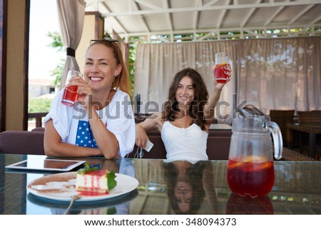 Young two happy women best friends enjoying recreation time while sitting in coffee shop in summer day, cheerful hipster girls with beautiful smiles posing while relaxing together in cozy restaurant  - stock photo