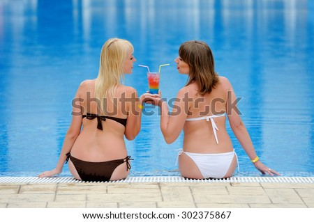Young two womans in a bikini at the swimming pool - stock photo