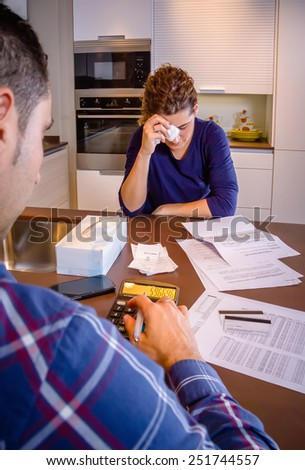 Young unemployed husband reviewing the bills and his desperate wife crying by their debts. Financial family problems concept. - stock photo