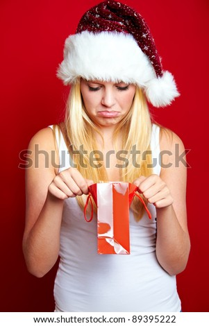 young unhappy blond girl with christmas present - stock photo