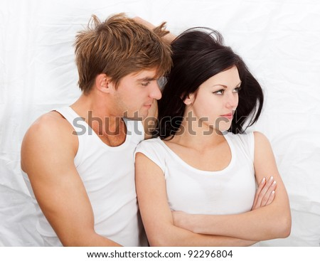 young upset couple lying in a bed, having problem. Divorce and separation conflict sad looking at camera, negative emotions concept, top view. - stock photo