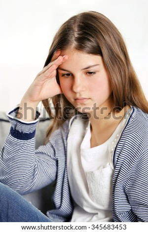 Young upset girl sitting on the sofa in her room - stock photo