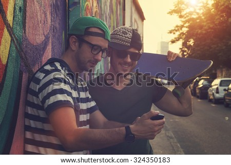 Young urban guys using a smartphone outdoors. - stock photo