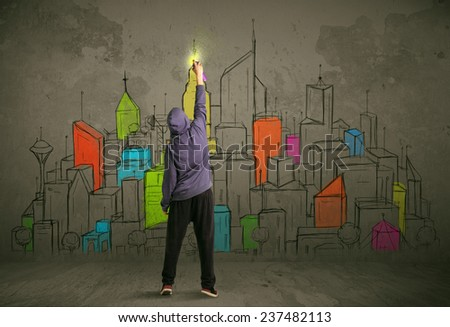 Young urban painter drawing colorful city  on the wall - stock photo