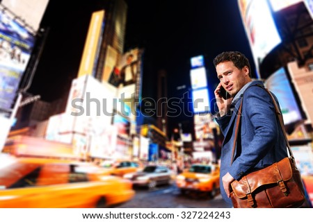 Young urban professional business man talking on smart phone onTimes Square, Manhattan, New York City. Young hip male businessman in casual suit in at night outdoors. - stock photo