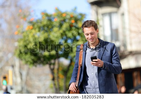Young urban professional man using smart phone. Businessman holding mobile smartphone using app texting sms message wearing jacket on Passeig de Gracia, Barcelona, Catalonia, Spain. - stock photo