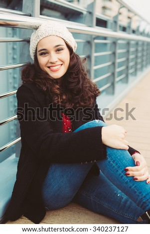 Young urban winter woman sitting on the floor smiling - stock photo